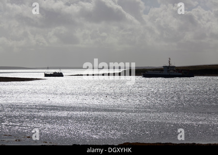 Islands of Orkney, Scotland. Picturesque silhouetted view of ferries leaving the Houton ferry terminal in the Bay - Stock Photo