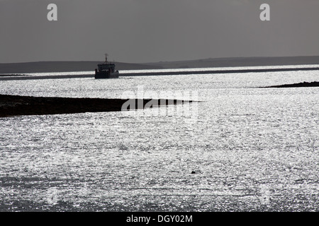 Islands of Orkney, Scotland. Picturesque silhouetted view of a ferry leaving the Houton ferry terminal in the Bay - Stock Photo