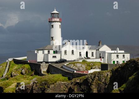Fanad Head Lighthouse on rocky cliff, rain shower, County Donegal, Ireland, Europe - Stock Photo
