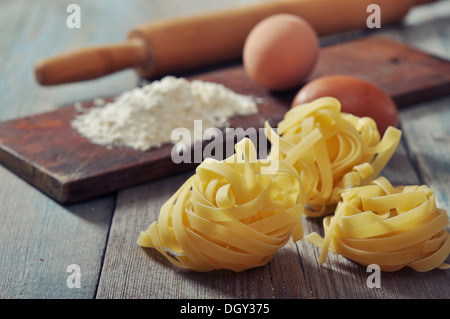 Flour, pasta and rolling-pin on wooden background  - Stock Photo
