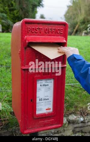 posting letter in traditional red post office box - Stock Photo
