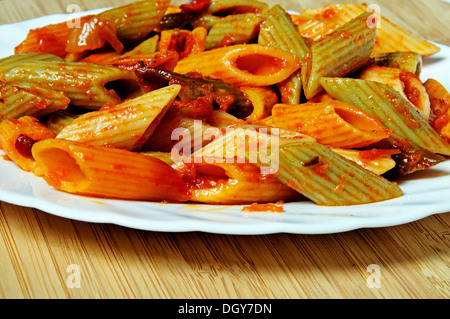 Multi-coloured Penne pasta in tomato sauce. - Stock Photo