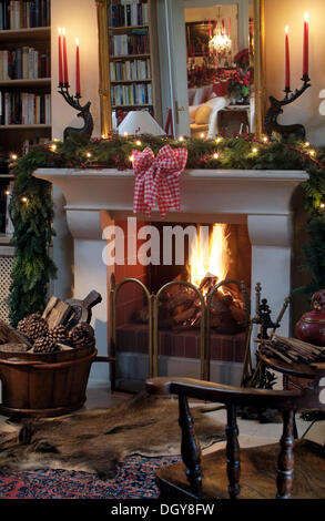 Burning, open fireplace with Christmas decorations in a stylish reading room - Stock Photo