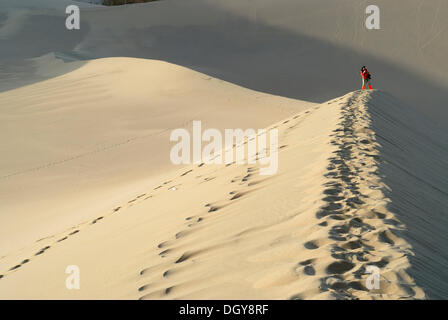 Young Chinese woman taking photographs on the sand dunes of the Gobi Desert, Silk Road, Gansu, China, Asia - Stock Photo