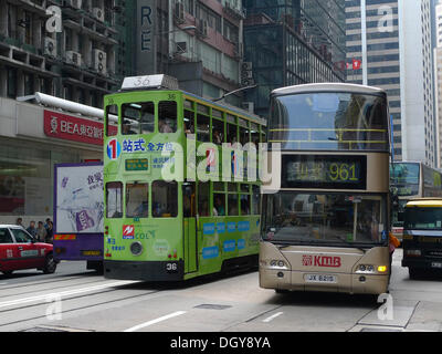 Light-green double-decker tram and bus on Queensroad in Hong Kong, China, Asia - Stock Photo