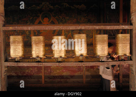 Prayer wheels and a Tibetan pilgrim in Jokhang Temple, Lhasa, Tibet, China, Asia - Stock Photo