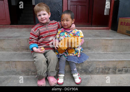 Encounters in Tibet, young European girl hugging a little Tibetan girl and her teddy-bear on stone steps, Lhasa, - Stock Photo