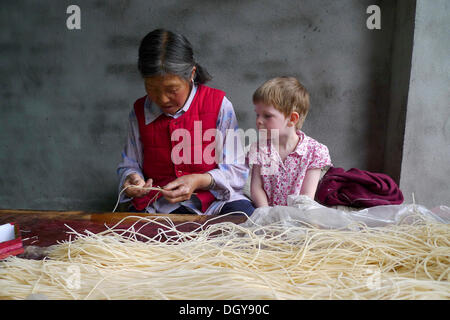 Encounters in China, young European girl watching on old Chinese woman making incense sticks, Moxi, Hailuogou, Sichuan, China