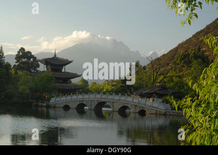 Pagoda, pavilion and Chinese bridge in the Black Dragon Pool Park, in the back the Jade Dragon Snow Mountain, 5596m - Stock Photo