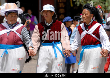 Three women in traditional costume of the Naxi minority holding hands and dancing on the main square in Lijiang, - Stock Photo