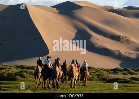 Group of tourists riding on camels towards the great sand dunes of Khorgoryn Els in the Gobi Desert - Stock Photo
