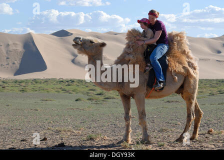 Young woman with red scarf sitting with a four-year-girl on a white camel in front of the large sand dunes Khorgoryn - Stock Photo