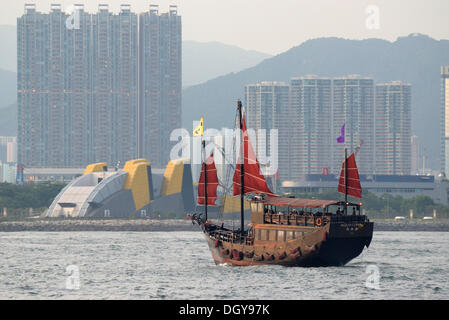 Hong Kong in the evening light with skyscrapers, tower buildings and a Chinese junk with red sails cruising from - Stock Photo