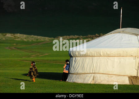 3 and 5-year-old Mongolian girls in front of yurts, yurt camp or ger camp, grasslands at the Orkhon waterfall in - Stock Photo