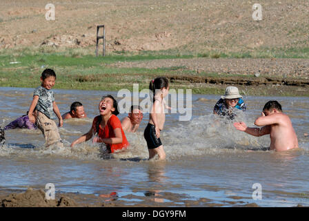 Bathing children and adults of a Mongolian extended family, splashing each other with water in the Ongi river, Oemnoegov - Stock Photo