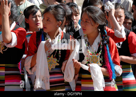 Tibetan girls wearing traditional costumes holding good luck scarves, Tibetan Khatags, waiting for His Holiness - Stock Photo