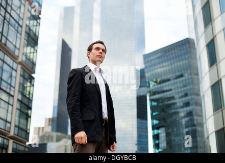 young businessman on skyscrapers background - Stock Photo