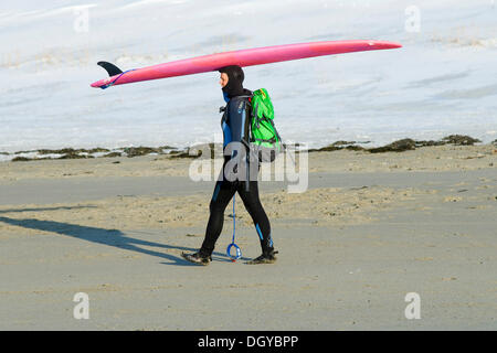 Surfer carrying surfboard on his head, ski surfing, beach of Unnstad, Island of Vestvågøya, Lofoten Islands, Northern - Stock Photo
