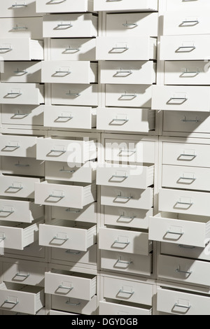 A white cabinet with drawers opened at varying degrees - Stock Photo