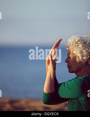 Old woman stretching her arms by the sea. Senior caucasian woman exercising on beach in morning. Fitness and healthy - Stock Photo