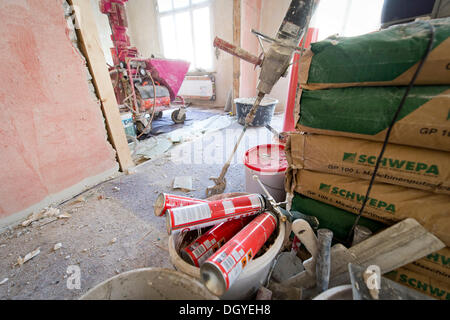 Plastering machine for plastering interior walls, bags of plaster for machine application, renovation of an old - Stock Photo