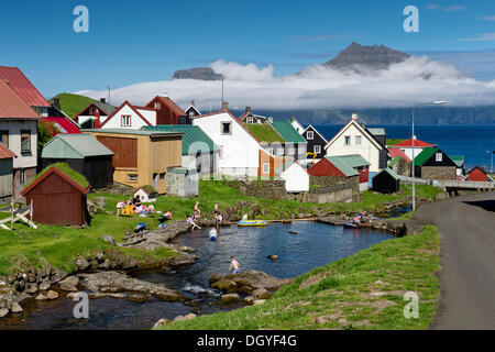 Village with typical colourful houses, children playing in a stream at front, Gjogv, Eysturoy, Faroe Islands, Denmark - Stock Photo