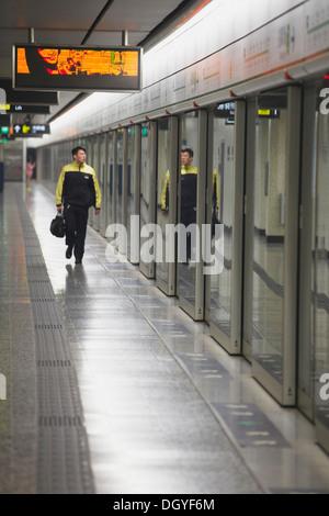 Train driver walking along platform in Mong Kok MTR station, Kowloon, Hong Kong, China - Stock Photo