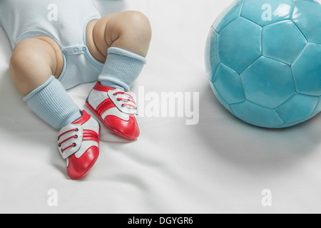 A baby boy wearing baby soccer shoes lying next to a soccer ball - Stock Photo