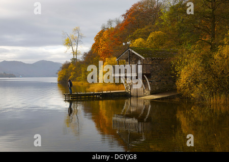 Man on jetty at Ullswater Boat House autumn Ullswater Lake District National Park Cumbria England United Kingdom. - Stock Photo