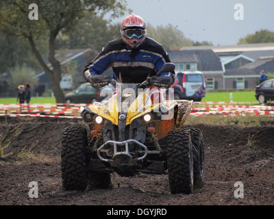 Powerful large quad riding on dirt track during the yearly enduro rallye event in Ruurlo, Gelderland, the Netherlands - Stock Photo