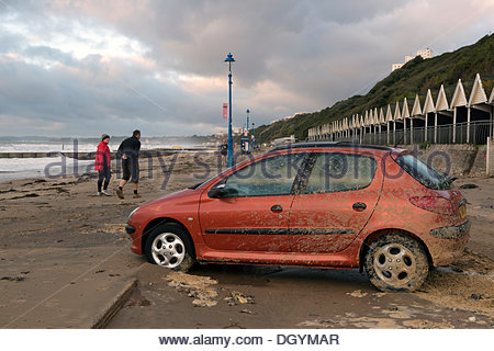 Bournemouth, UK, 28th October 2013. A car left on the beach is covered in sand after St Jude's Day storm in Boscombe. - Stock Photo