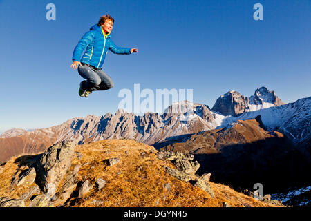 Young woman jumping, Mt Kalkkoegel, Tyrol, Austria, Europe - Stock Photo