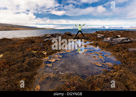 Reflection of a young woman in a pond, Westfjords, Iceland, Europe - Stock Photo