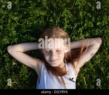 happy little girl dreaming on the grass and enjoying summer - Stock Photo