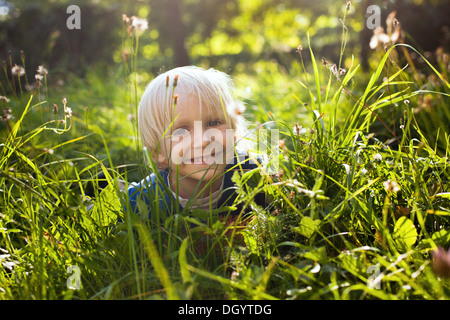 blond happy little boy in the grass - Stock Photo