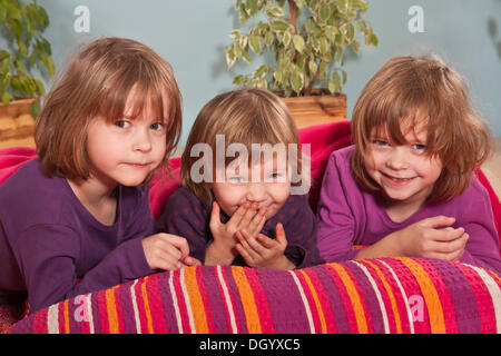 Girls, twins, six years, and three-year-old girl in the middle - Stock Photo