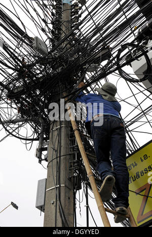 Man climbing up a ladder to fix power lines, pylon, Chiang Mai, Thailand, Asia - Stock Photo