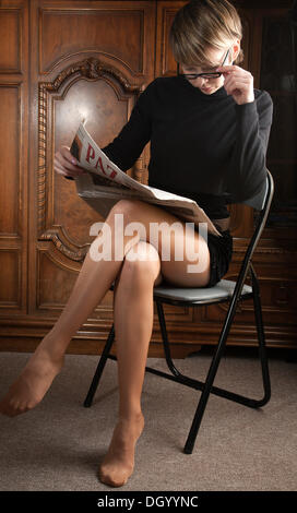 Young woman in pantyhose and glasses reading a newspaper - Stock Photo