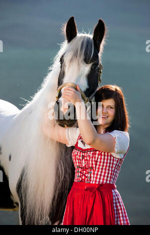Young woman wearing a dirndl cuddling with a Gypsy Vanner or Tinker horse, pinto, black and white, North Tyrol, - Stock Photo