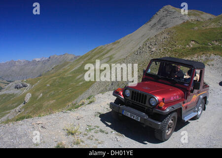 Off-road vehicle driving on the road to the Col de la Bonette mountain pass, highest paved road in Europe - Stock Photo