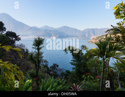 Sunrise at Lake Atitlan in Guatemala formed from volcano crater. Town of San Pedro La Laguna in distance - Stock Photo