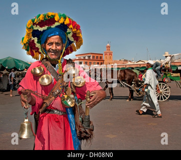 Moroccan water seller in traditional dress Jamaa el Fna square market place in Marrakesh's Medina quarter Morocco - Stock Photo