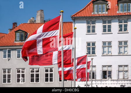 Danish flag waving, in the Nyhavn district of Copenhagen, Denmark - Stock Photo