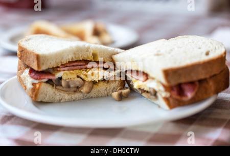 A halved bacon, egg and mushroom sandwich on a plate, London, England, UK. - Stock Photo