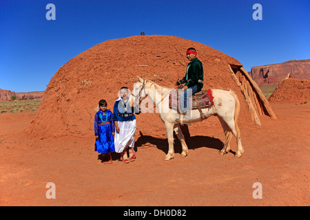 Navajo Indian family with a horse, in front of a Navajo Hogan, a traditional residence, Monument Valley, Utah, United - Stock Photo