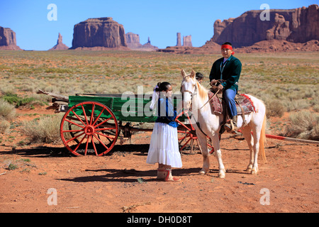 Navajo Indians, man and woman with a horse in front of a carriage, Monument Valley, Utah, United States - Stock Photo