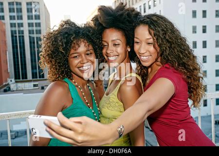 Mixed race women taking self-portrait on urban rooftop - Stock Photo