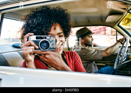 Woman using vintage camera in car - Stock Photo