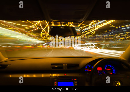 view through the windscreen of a moving car with motion blur and different sections on the motorway with road works - Stock Photo