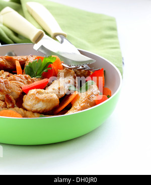 fried chicken (turkey) fillets with vegetables in a pan - Stock Photo